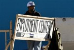 A day laborer stands behind a sign for an employment center in San Diego, January 6, 2011.